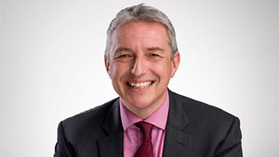 Ian Walker is a white man with short grey hair. He is smiling and wears a charcoal grey suit, a pink shirt and a red patterned tie.