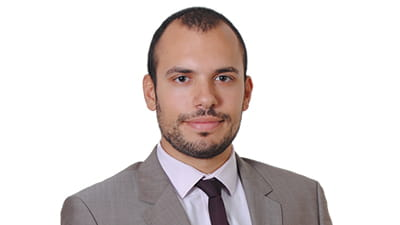 Marios Kontos is a tanned man with cropped black hair and stubble. He wears a light grey suit, white shirt and dark tie.