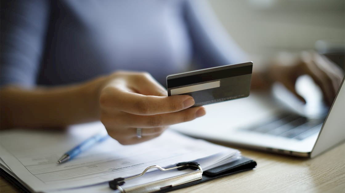 Woman using credit card to pay invoices