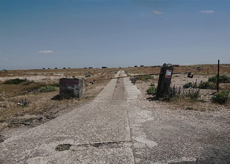 Barrier on disused road through empty field in Dungeness, England