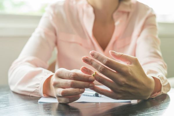 A young woman is pulling her wedding ring from finger. She is sat at a desk and wears a peach shirt, with a form and pen in front of her. Her face is cropped out of the frame.