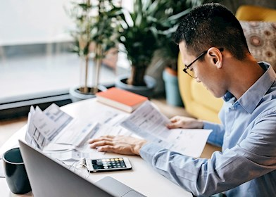 Man using calculator and laptop to give tax advice