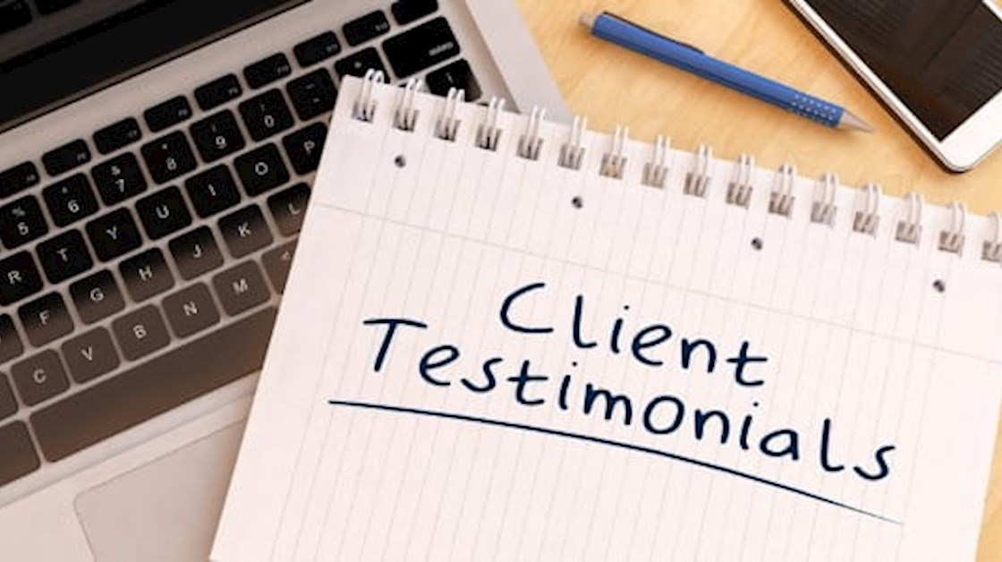 Client testimonial heading on notepaper resting on keyboard