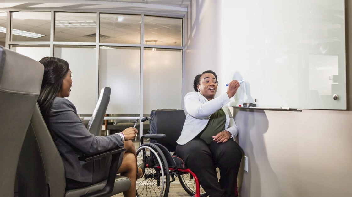 Disabled business person writing on board