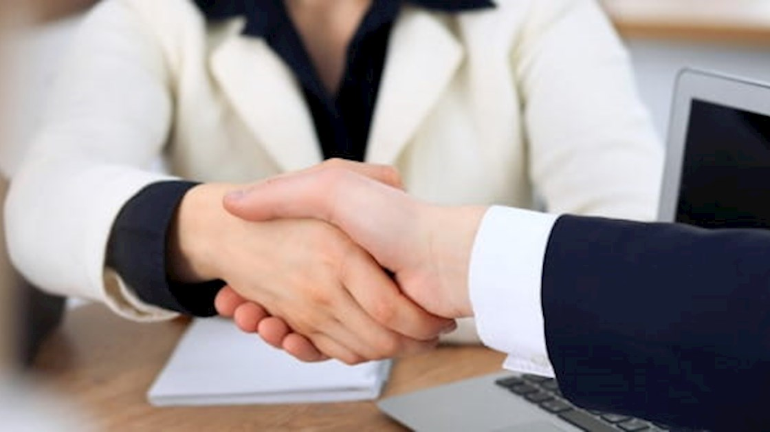 Woman in white jacket shaking hands with man in dark suit
