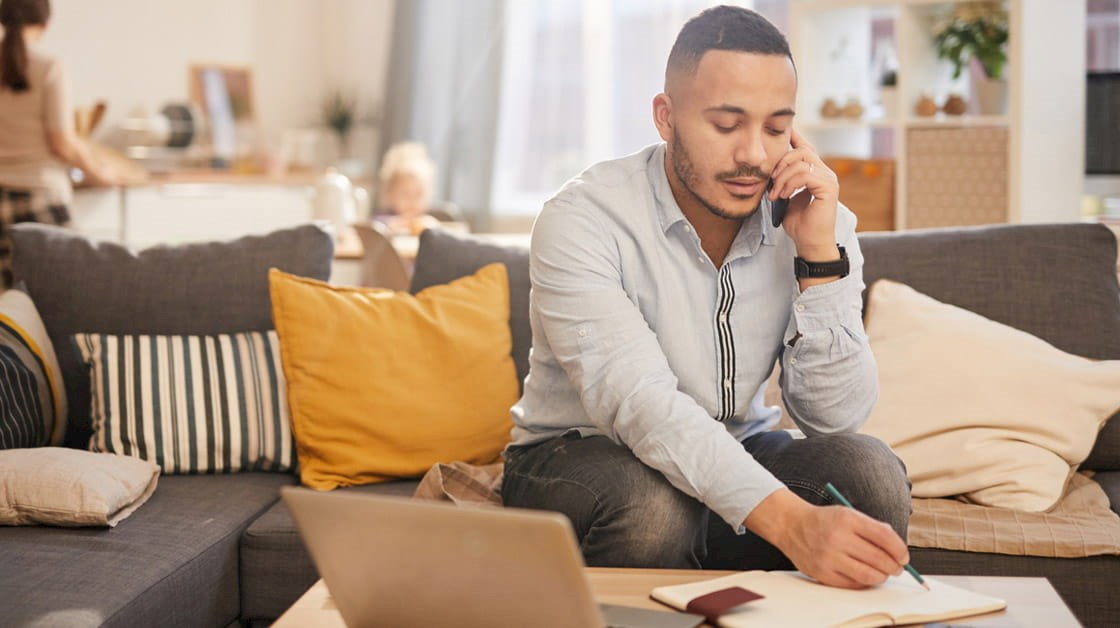 Man working from home on laptop which family in the background
