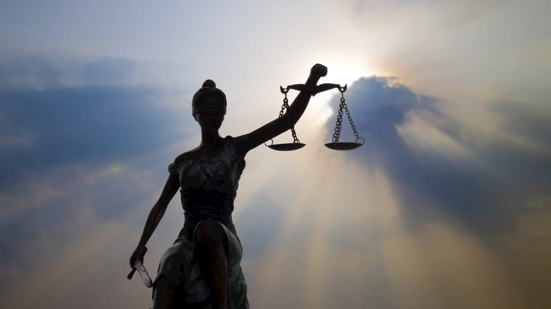 Lady Justice statue with rays of light shining through