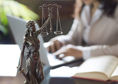 Lady Justice statue with woman working in the background on laptop