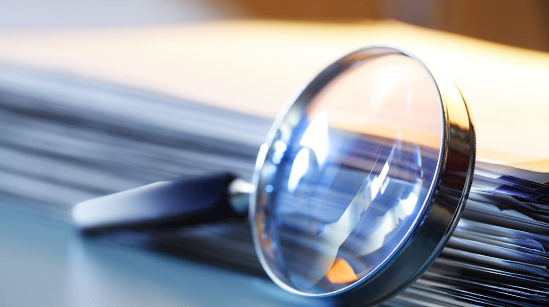 magnifying-glass-by-stack-of-papers