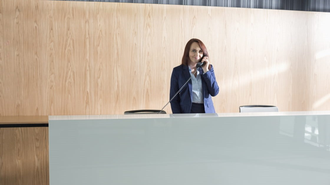 Receptionist answering the phone at front desk of office