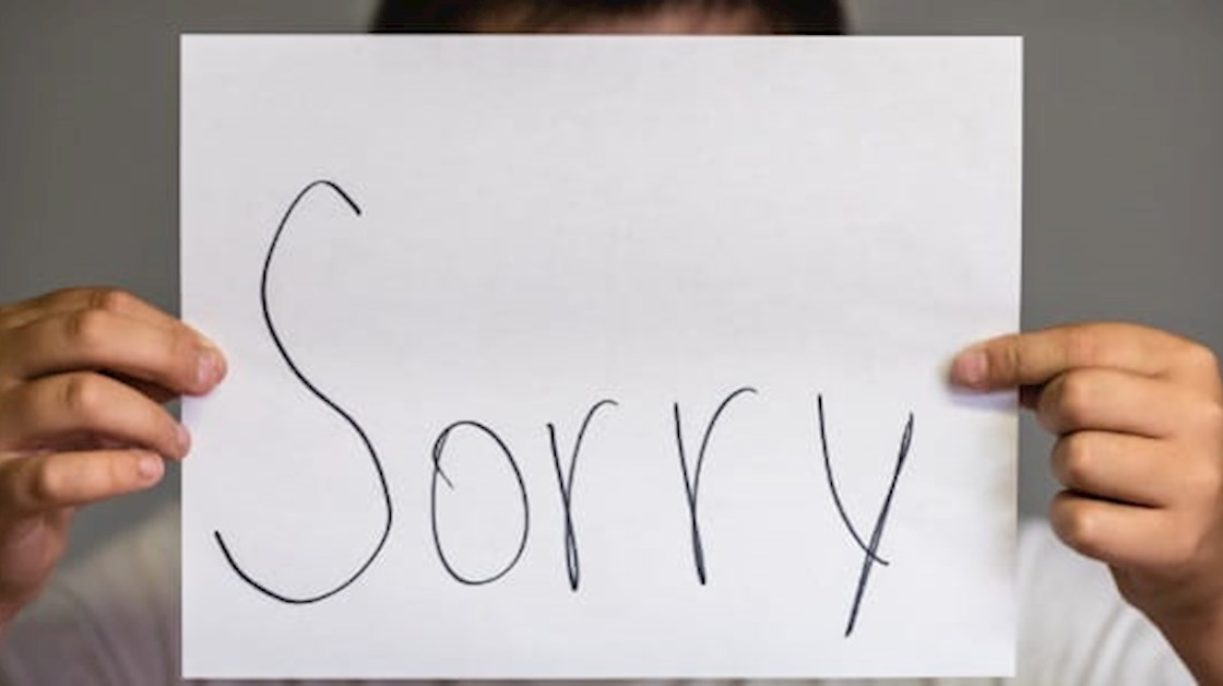 Sorry card held by person