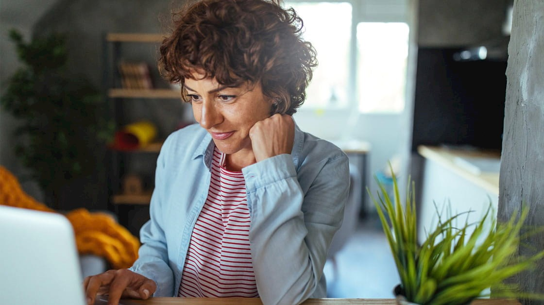 Woman at home sat at desk working on a laptop