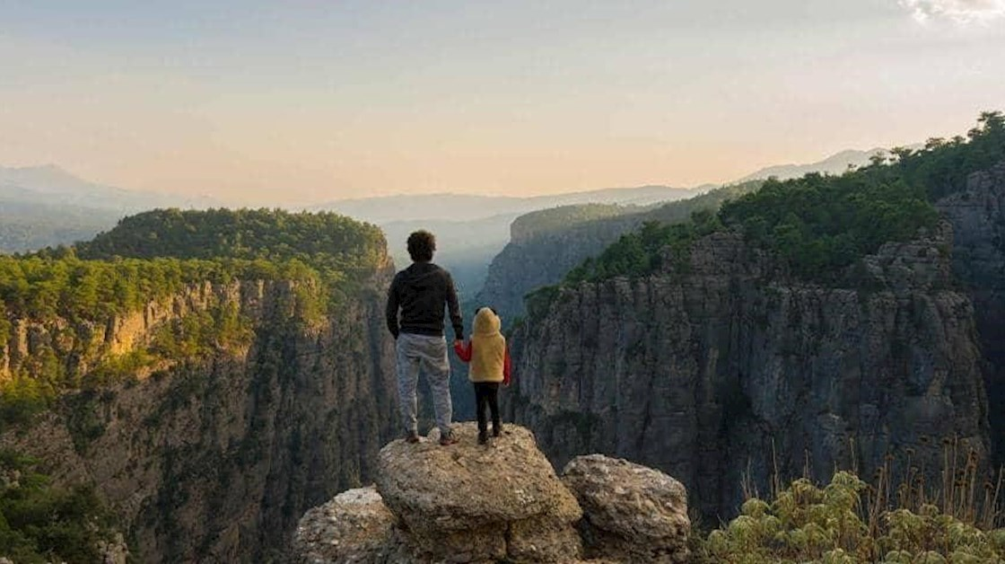 Man and child looking out over the mountains