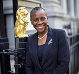 I. Stephanie Boyce stands outside the Law Society building wearing a dark suit. Her hair is cropped and she is smiling widely.
