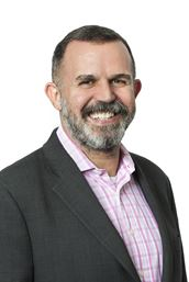 Patrick is a white man with short dark hair and a salt and pepper beard. He wears a pink patterned shirt and grey suit jacket, and he is smiling.