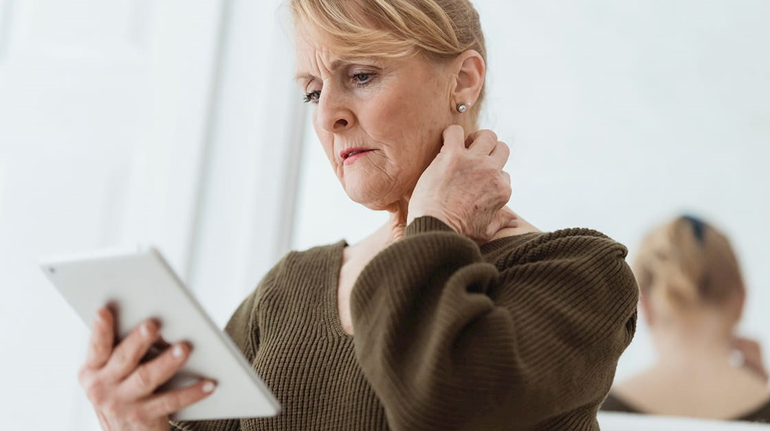Woman holding tablet, one hand on her neck