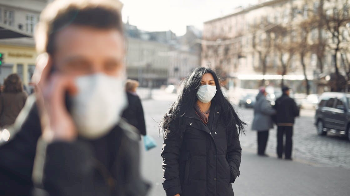 People in face masks standing in street