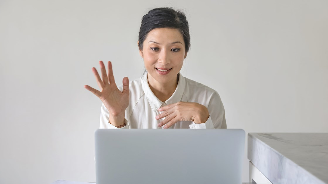 An Asian woman with dark hair tied back wearing a white shirt waves at a laptop in front of a plain white background.