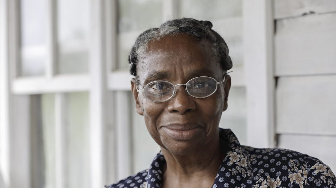 An older Black Caribbean woman wearing glasses. She is smiling and wearing a floral shirt.