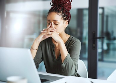 Anxious, stressed woman working at office desk