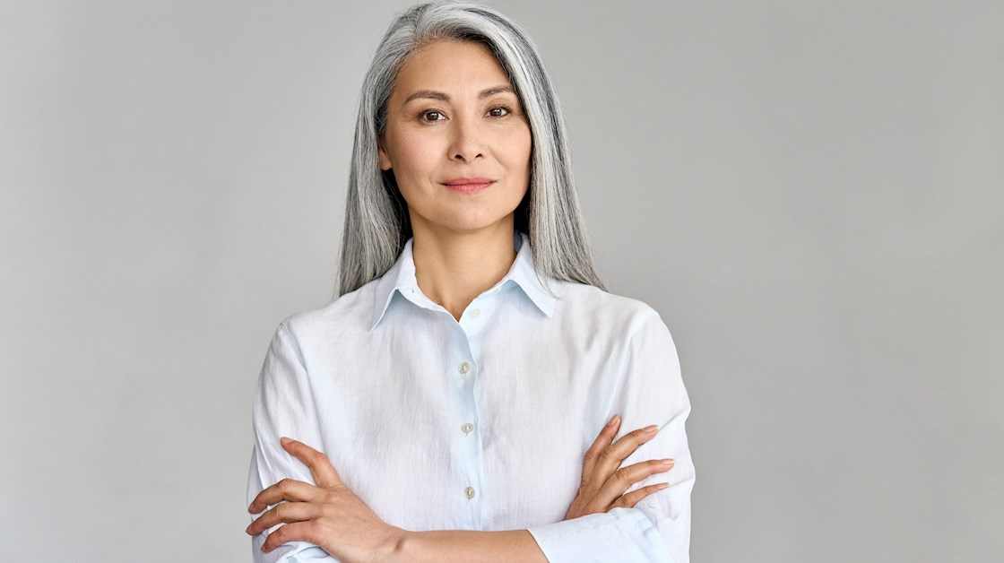 Asian woman with long grey hair stands in front of a light grey background. She is wearing a white shirt and her arms are folded.