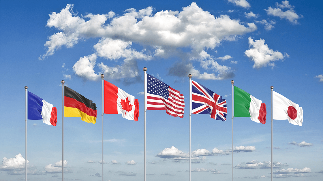 Flags of G7 countries flying against blue sky