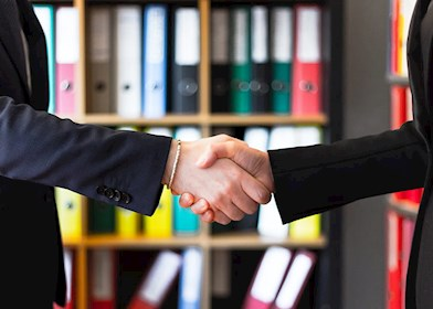 Two people shaking hands in front of shelves