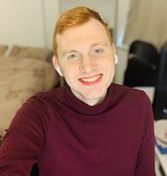 Joe is a white non-binary person with short red hair. They are wearing a red jumper and have a big smile.