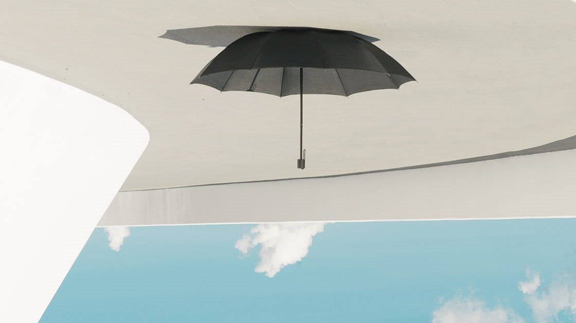 Upside down umbrella on sand, with blue sky below