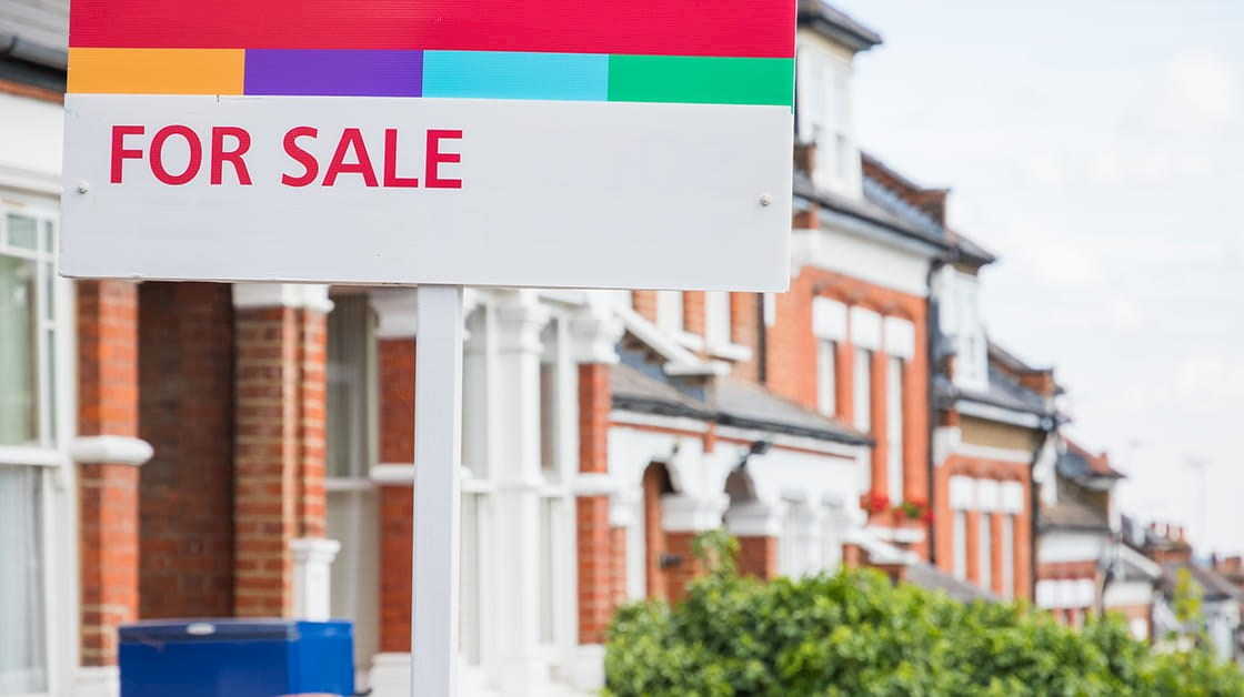 'For sale' sign in front of house on red-brick terraced street
