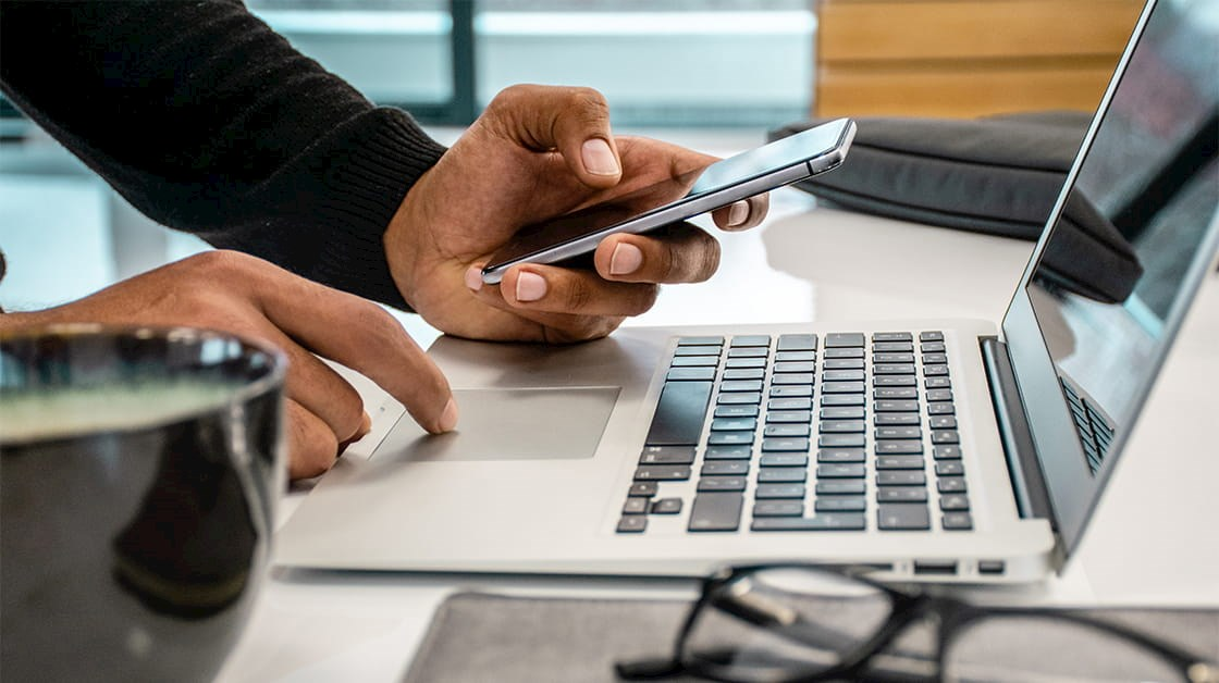 Man using laptop and smartphone to produce report